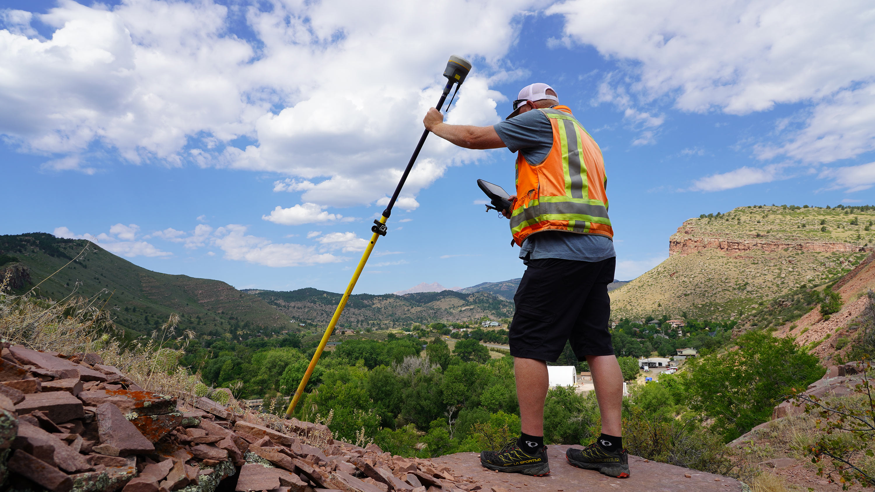 Surveyor using a tilted GNSS rover at the edge of a steep embankment