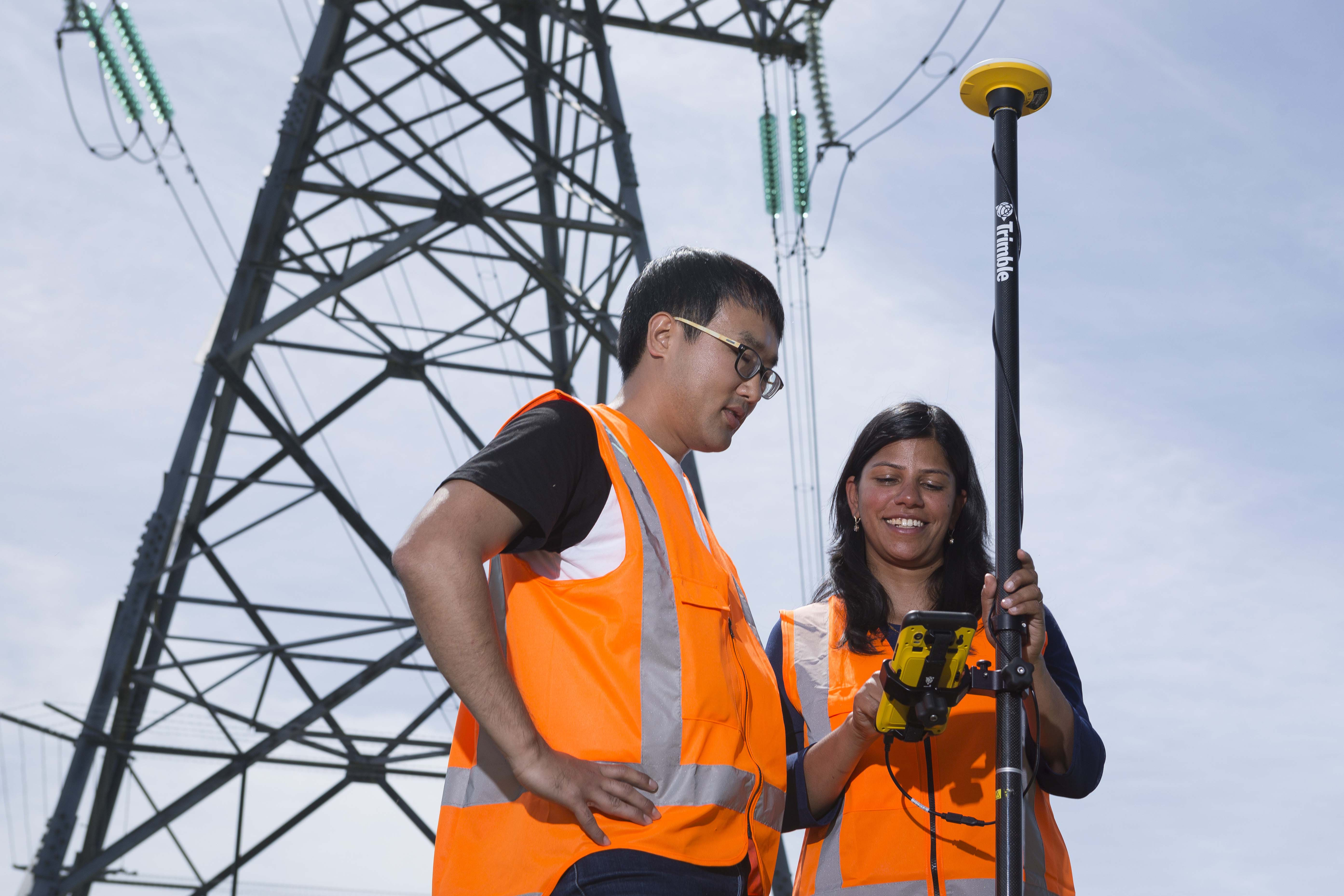 Image of man and women standing by pylon with GIS data collection solution on rangepole