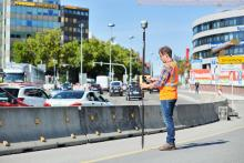 Man standing in a city street surveying with a GNSS rover unit